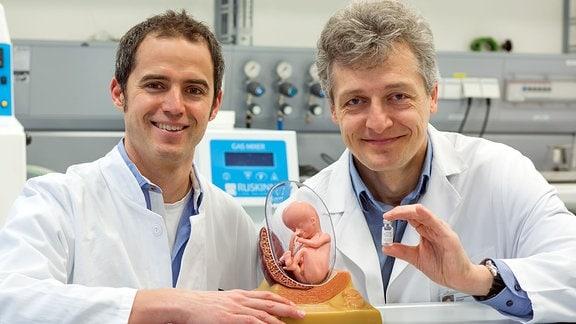 Mit der Injektion eines Ersatzproteins in die Fruchtblase haben Prof. Dr. Holm Schneider (r.) und PD Dr. Florian Faschingbauer eine erbliche Entwicklungsstörung korrigiert, die bislang unheilbar war