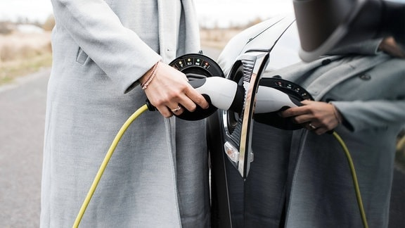 Hand einer Frau beim Einstecken des Ladekabels für ihr Elektroauto