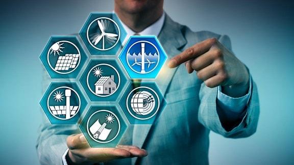 Ein Mann balanciert digitale Piktogramme erneuerbarer Energiequellen auf der Hand.