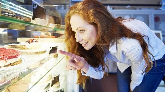 Frau vor einem Kuchenregal.