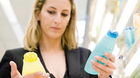 Eine Frau hat zwei Flaschen in den Händen und muss sich entscheiden.