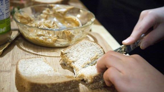 Ein Sandwitch mit Erdnussbutter wird zerschnitten.