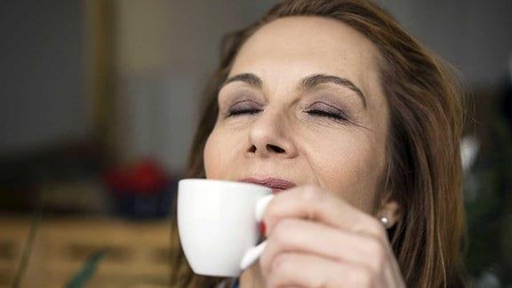 Eine Frau, die den Espresso aus der Tasse genießt.