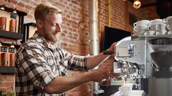 Ein Mann an einer Espressomaschine