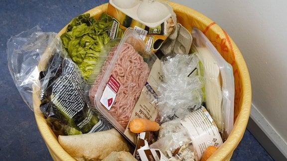 Lebensmittel liegen in einem Mülleimer.