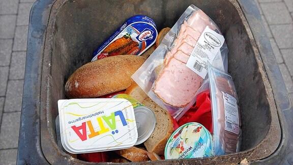 Lebensmittel in einer Muelltonne.