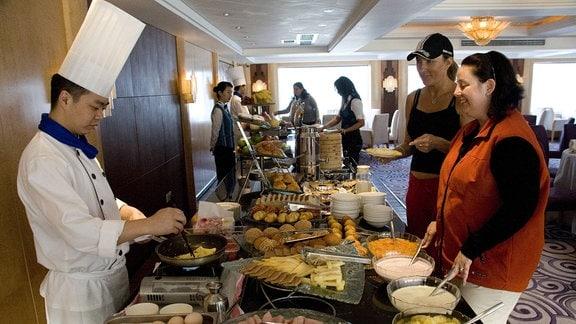 Koch und Gäste an Buffet