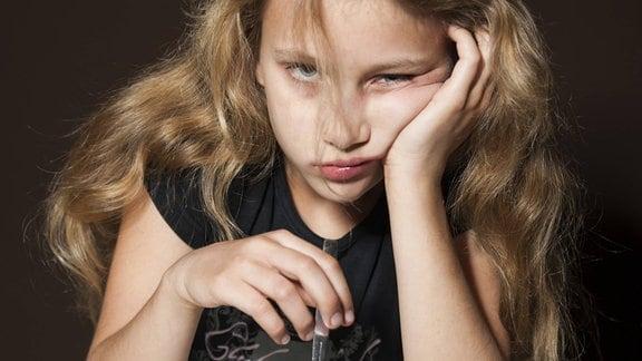 Ein Mädchen schaut grießgrämig in die Kamera und hat einen Teller Spinat vor sich stehen.
