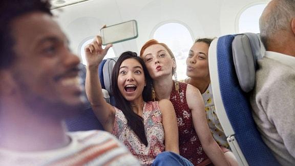 Menschen verschiedener Ethnien in einem Flugzeug, zwei Frauen machen ein Selfie -- Perspektive aus den Sitzreihen, Person im Vordergrund unscharf.
