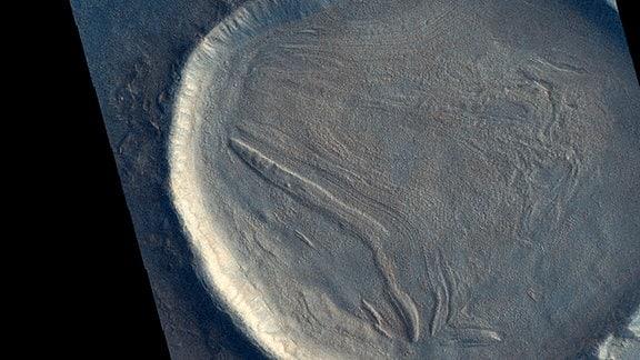 Ein großer Krater auf dem Mars mit faltiger Landschaft darin.