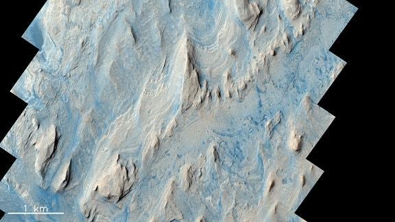 Der Gale-Krater auf dem Mars enthält helle Felsformationen und blaue Sandschichten dazwischen.
