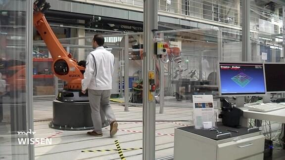 Ein Techniker geht zu einem Indutrieroboterarm. Rechts im Bild sind Computermonitore zu sehen.