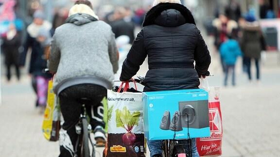 Passanten transportieren ihre Einkäufe auf Fahrrädern in der Innenstadt.