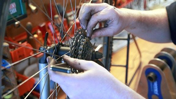 Ein Mann hängt eine Fahrradkette auf die Zahnräder.
