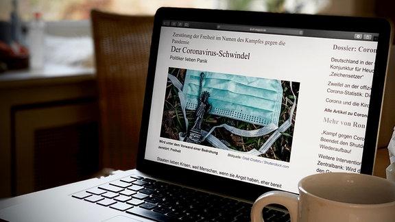 """Ein Laptop auf einem Tisch, Artikel aufgerufen mit Überschrift """"Der Corona-Schwindel"""", Kaffeetasse, dunkle Farben, unscharfer Hintergrund."""