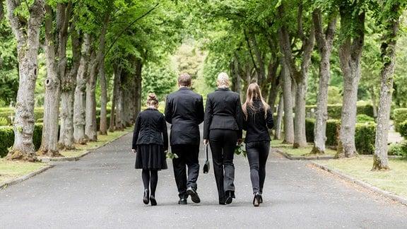 Familie in Schwarz auf dem Friedhof