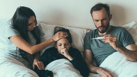 Familie mit Kind liegt krank im Bett