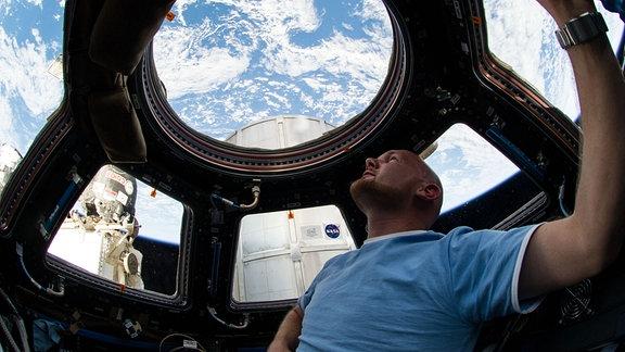 Alexander Gerst schaut aus der Raumstation auf den blau leuchtenen Erdball.