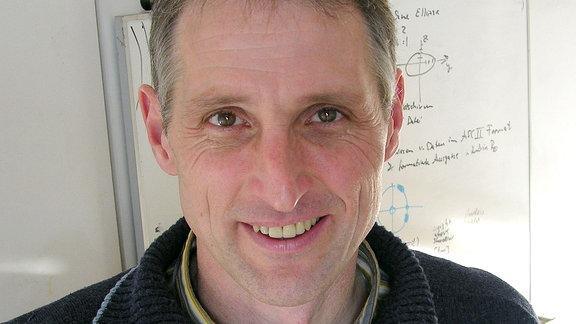 Ein Mann schaut in die Kamera, hinter ihm eine Tafel mit Formeln.