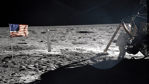 Ein Astronaut vor einer Mondlandekapsel, links die Flagge der USA.