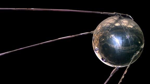 Weltraumaufnahme von Satellit Sputnik 1. Zu sehen ist eine Kugel mit vier langen silbernen, langen, dünnen Armen im Weltall