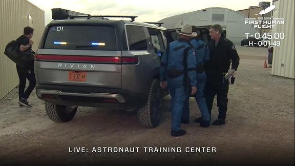 Die Astronaut:innen auf dem Weg zu ihrem ersten Raumflug. Hier befinden sie sich beim Einsteigen in das Transportmobil zur Startplattform.