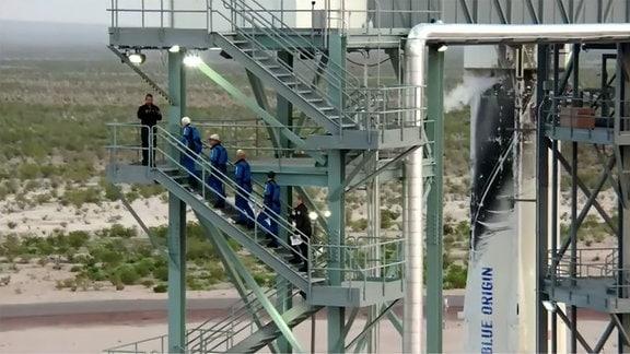 Die vier Astronauten steigen die Treppen der Startrampe hinauf