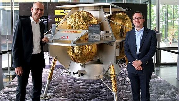 """Arjan Sissing (DHL Markenchef, links) und Dan Hendrickson (Vice President of Business Development bei Astrobotic, rechts) vor einem Modell vom """"Peregrine Luna Lander"""". Dieses Mondfahrzeug soll Ende 2021 auf dem Mond landen."""