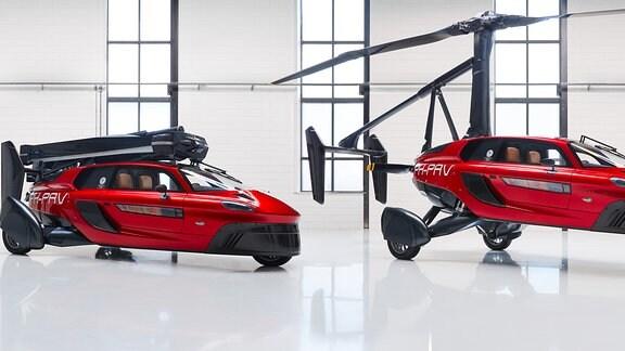 Zwei rote Fahrzeuge - eins mit eingeklappten und eins mit ausgeklapptem Rotor - stehen nebeneinander.