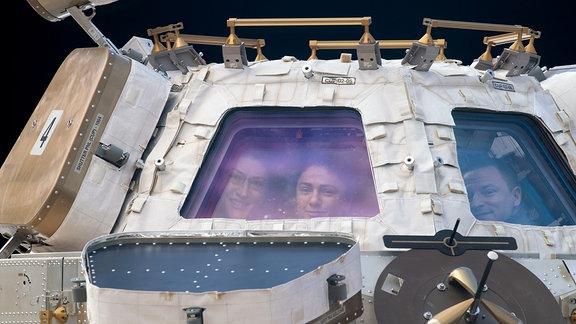 Zwei Astronautinnen und ein Astronaut schauen aus der Beobachtungskuppel der ISS