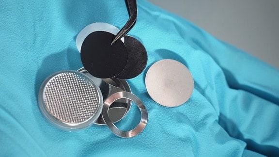 Eine Knopfzellenbatterie in ihre Bestandteile zerlegt.