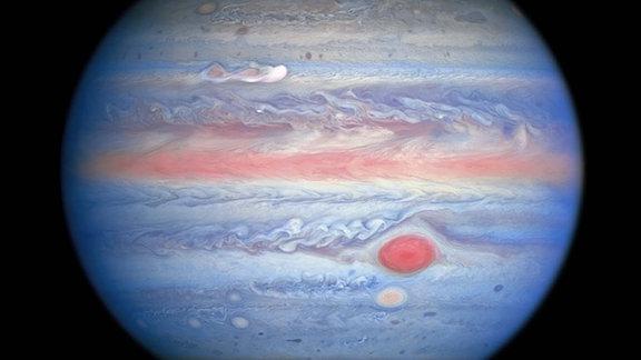 """Eine vom Hubble-Weltraumteleskop der NASA / ESA am 25. August 2020 durchgeführte Multiwellenlängenbeobachtung von Jupiter im ultravioletten / sichtbaren / nahen Infrarotlicht bietet Forschern eine völlig neue Sicht auf den Riesenplaneten. Die Nahinfrarot-Bildgebung von Hubble in Kombination mit ultravioletten Ansichten bietet einen einzigartigen panchromatischen Look, der Einblicke in die Höhe und Verteilung des Dunstes und der Partikel des Planeten bietet. Dies ergänzt Hubbles Bilder mit sichtbarem Licht, die die sich ständig ändernden Wolkenmuster zeigen.  Auf diesem Foto sehen die Teile der Jupiter-Atmosphäre, die sich in größerer Höhe befinden, insbesondere über den Polen, rot aus, da atmosphärische Partikel ultraviolettes Licht absorbieren. Umgekehrt repräsentieren die blau gefärbten Bereiche das ultraviolette Licht, das vom Planeten reflektiert wird.  Ein neuer Sturm oben links, der am 18. August 2020 ausbrach, erregt die Aufmerksamkeit der Wissenschaftler in dieser Multiwellenlängenansicht. Die """"Klumpen"""" hinter der weißen Wolke scheinen ultraviolettes Licht zu absorbieren, ähnlich dem Zentrum des Großen Roten Flecks und des Roten Flecks Jr. direkt darunter. Dies liefert Forschern mehr Beweise dafür, dass dieser Sturm auf Jupiter länger andauern kann als die meisten Stürme."""
