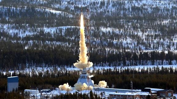 Eine Rakete startet vor Winterlandschaft