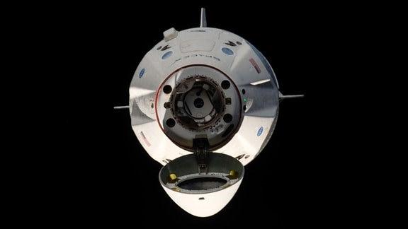 Ein Raumschiff im Weltall mit geöffneter Andockklappe.