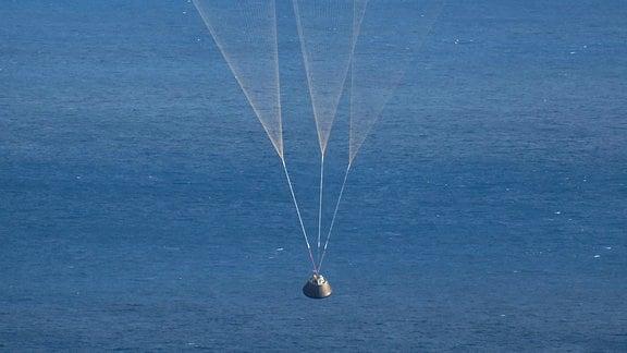Raumkapsel mit Fallschirm am Himmel