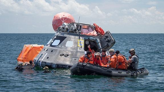 Raumkapsel im Meer, Schlauchboote mit mehreren Menschen