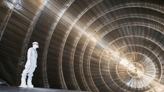 Ein Mann im Schutzanzug steh in einem großen silbernen Zylinder