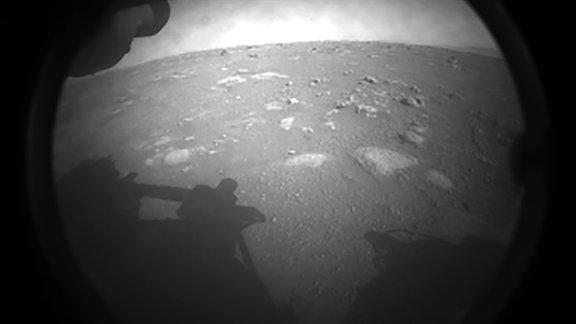 Eine schwarz-weiß Aufnahme der Marsoberfläche. Man erkennt den Schatten des Rovers und die staubige Oberfläche des Mars. An einigen stellen befinden sich flache Steine.