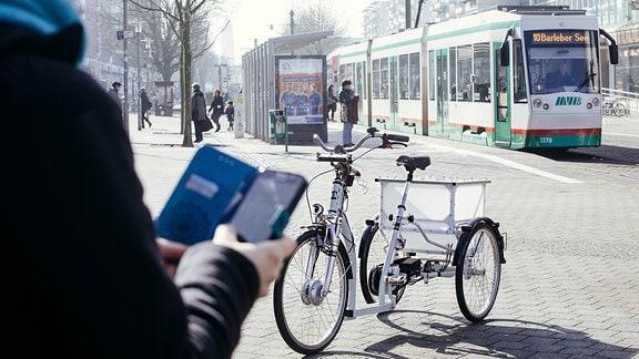 Ein selbstfahrendes E-Bike mit drei Rädern steht auf einem Platz. Im Hintergrund ist eine Straßenbahn zu sehen.