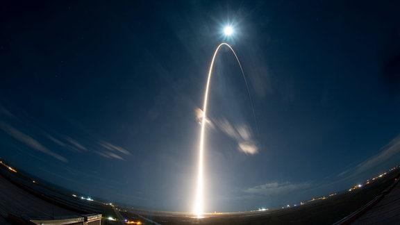 Ein Feuerkreis am Himmel zeigt die Startbahn einer Rakete