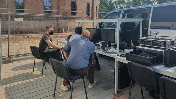 Das Team von MDR Wissen hinter den Kulissen. Drei Männer und Equipment sind vor einem Bauzaun zu erkennen. Das Bild wurde vor dem Planetarium Halle (Saale) aufgenommen