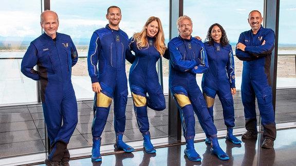 Vier Männer und zwei Frauen in blauen Uniformen vor einem Fenster