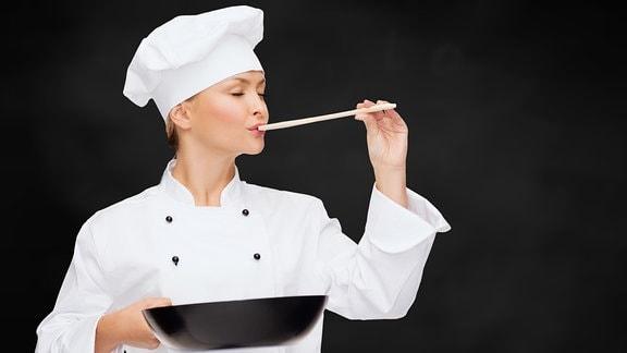 Köchin mit Pfanne und Löffel kostet Essen