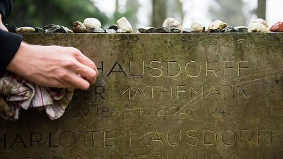 Der Grabstein von Felix Hausdorff wird gereinigt.