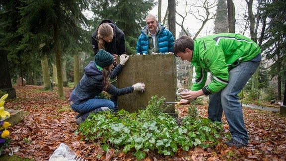 Vier Personen pflegen ein Grab.