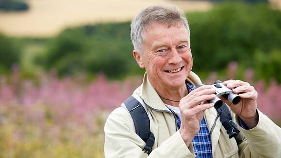 Ein Mann mit Fernglas steht in der Natur.