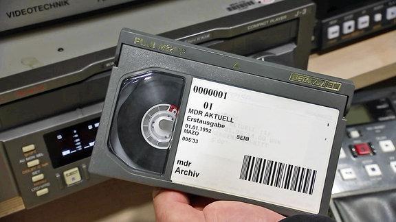 Eine Hand hält eine Kassette mit Aufschrift 'MDR aktuell Erstausgabe 01.01.1992'