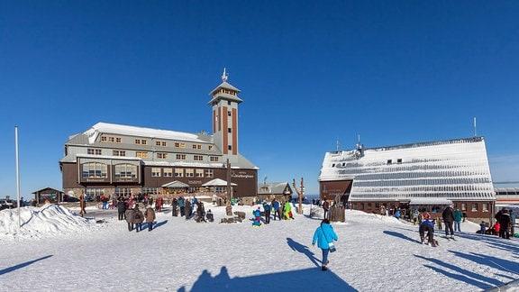 Skifahrer und Spaziergänger laufen am 30.12.2016 vor dem Fichtelberghaus auf dem Fichtelberg in Oberwiesenthal.