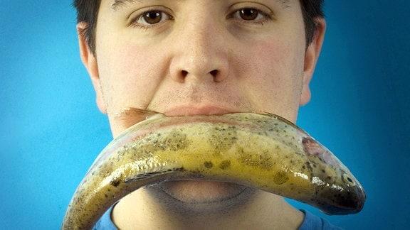 Junger Mann mit einem Fisch im Mund.