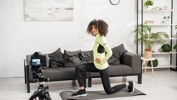 Amerikanische Video-bloggerin macht Fitnessübung vor der Kamera